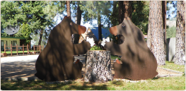 Two statues of bears over a wood stump